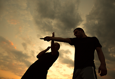 men fighting in front of a sunset